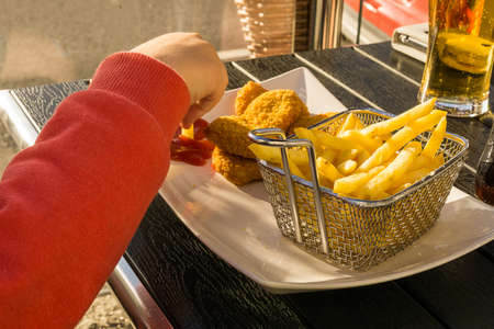 grabing: A young child is diping a french frie with his right hand in ketchup while eating chicken nuggets at a diner. Stock Photo