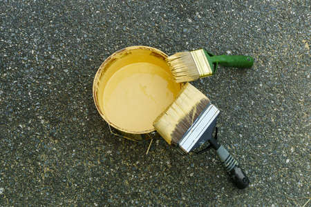 improvment: Two brushes dipped in yellow color leaned against the rim of a yellow paint can.