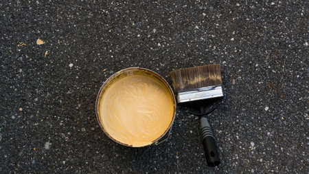 paintjob: A paint brush besides a can with yellow  acrylic latex paint.