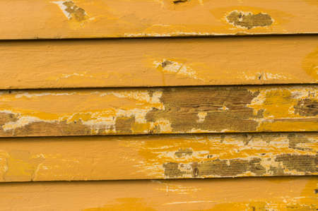 improvment: Facade planks where the loose cracked paint flakes has been scraped of so the bare wood is visible oiled and ready for repaint