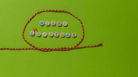 The words merry christmas, misspelled as cristmas, forming with letter pearls with different colours inside a string loop knot of a red and white yarn on a green background
