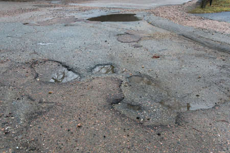 Water filled pot holes in the asphalt road.