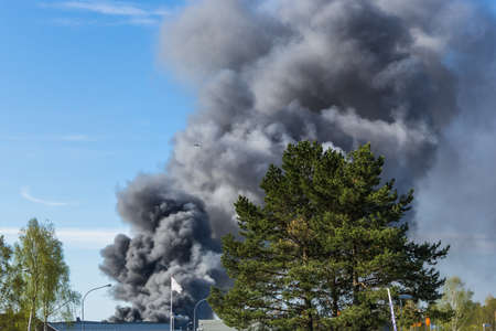 Thick grey and black smoke from a burning fire  is rising to the sky above the house roof tops. Stock Photo