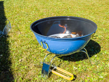 A blue and black barbeque grill with charcoal burning with orange flames waiting for the coal to be ready