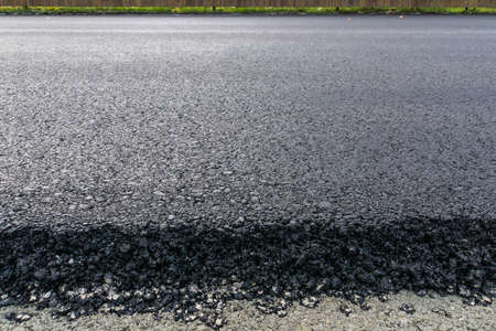 freshly laid black bitumen asphalt with a high edge to the gravel showing the structure.