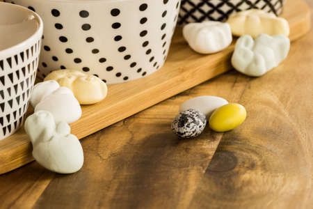 colorful easter candy eggs and animal shaped marshmallows on wooden surface besides bowls with black pattern on white shallow dof