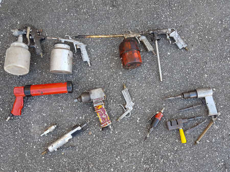 Many different old worn used air pressure tools on asphalt ground ground
