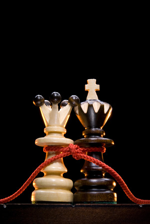 mutual: Chess  king and queen  on a chess board  An black background