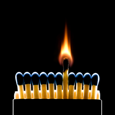 match box: Many dark blue matches on a black background  one match burns   Stock Photo