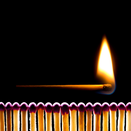 It is a lot of matches on a black background  One match burns  photo