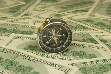Compass on a background of dollars  it is a lot of money   photo