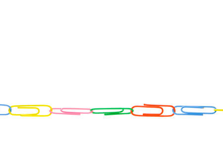 dependent: Color office paper clips on a white background.