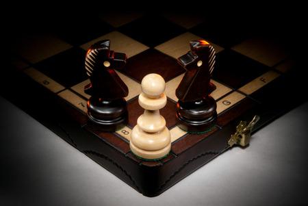Chessmen on a chess board. A dark background and art illumination. Stock Photo