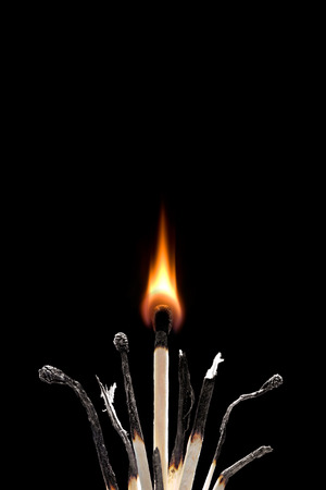 spoiled: The spoiled matches on a black background. One match burns.