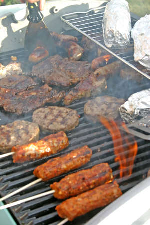 sizzling: Sizzling Meat on Smokey Summer Barbecue Stock Photo