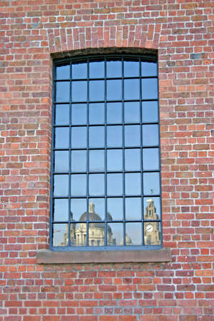 corner clock: Liver Building  and 3 Graces Reflected in Warehouse Window in Liverpool UK