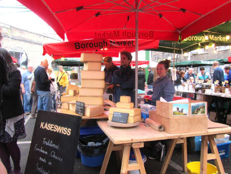 the stalls: LONDON - AUGUST 14: Unidentified visitors near a Swiss Cheese stall at Borough Market on August 14, 2010 in London. Borough Market is one of the largest gourmet food markets in London.