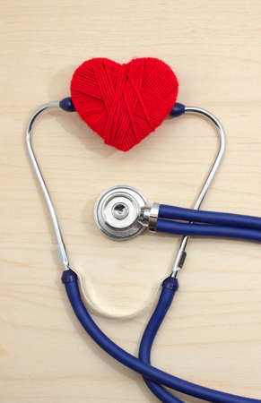 stethoscope and heart symbol of red thread on a wooden table