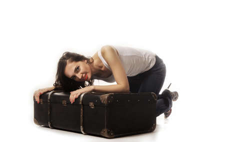 bent over: Beautiful woman with long brown hair bent over with a suitcase. Girl hugs a suitcase