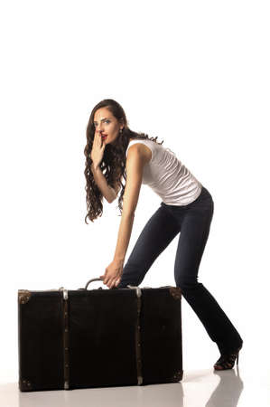 bent over: Beautiful woman with long brown hair bent over with a suitcase. Woman tries to steal a suitcase. Stock Photo