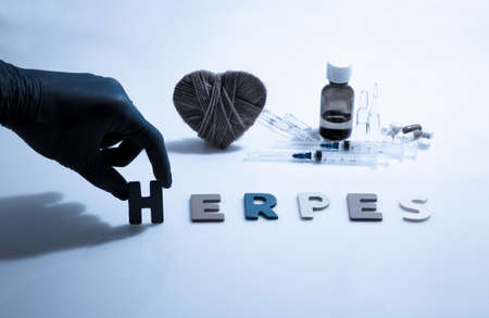 herpes: Hand and herpes word on the white background