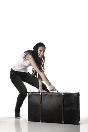 bent over: beautiful woman with long brown hair bent over with a suitcase