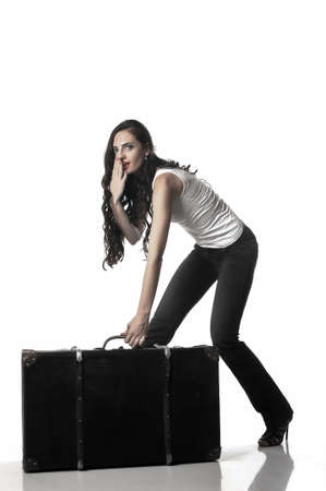 bent over: Beautiful woman with long brown hair bent over with a suitcase. Woman tries to steal a suitcase. Tinted photo Stock Photo