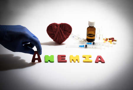anemia: Hand and anemia word on the white background
