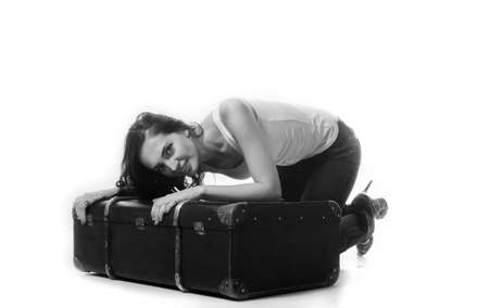 bent over: Beautiful woman with long brown hair bent over with a suitcase. In an embrace with a suitcase. Black and white photo