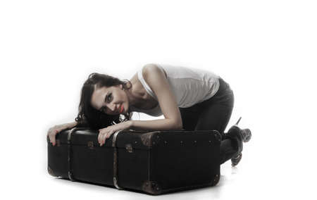 bent over: Beautiful woman with long brown hair bent over with a suitcase. Girl hugs a suitcase. Tinted photo Stock Photo