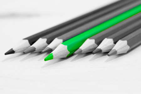 Green separated pencil on the gray background. Selective depth of field