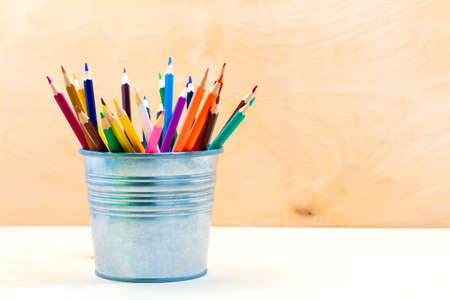 hued: Color pencils in tin can, on a wood table