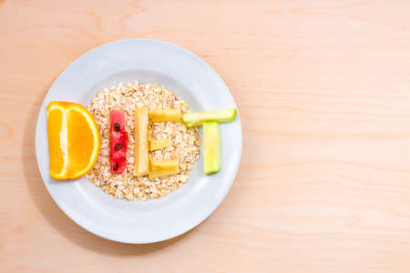starvation: white plate with the word diet of different fruits on a wooden table Stock Photo