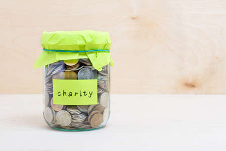 Financial concept. Coins in glass money jar with charity label. Wooden background Foto de archivo