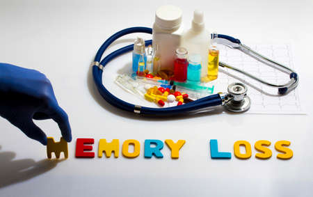 memory loss: Diagnosis - Memory loss. Medical concept with pills, injection, stethoscope, cardiogram and a syringe Stock Photo