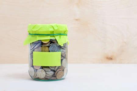 Concepto financiero. Monedas en el tarro de cristal con el dinero etiqueta. fondo de madera