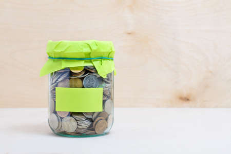 Financial concept. Coins in glass money jar with label. Wooden background