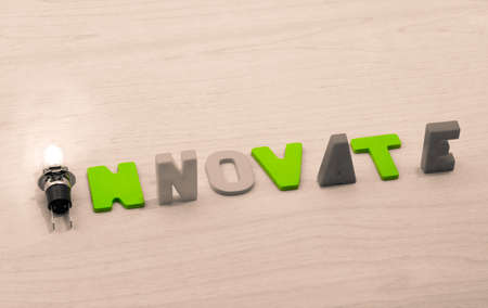The concept of innovate. Lamp and word innovate on a wooden background
