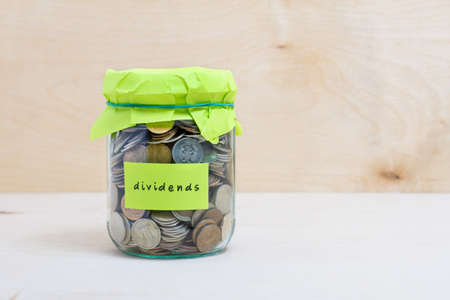 dividends: Financial concept. Coins in glass money jar with dividends label. Wooden background