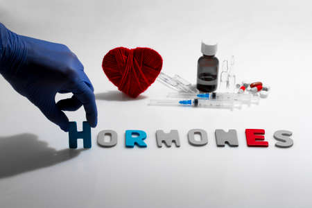 hormones: Hand and hormones word on the white background