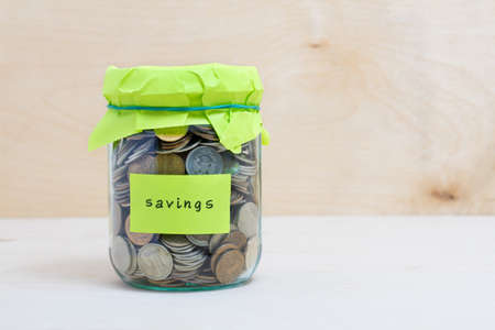 money jar: Financial concept. Coins in glass money jar with savings label. Wooden background Stock Photo