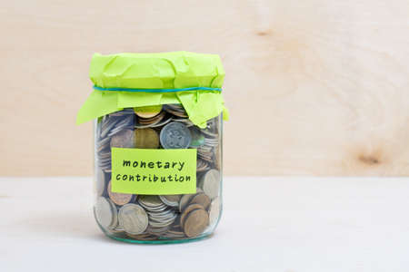 contribution: Financial concept. Coins in glass money jar with monetary contribution label. Wooden background