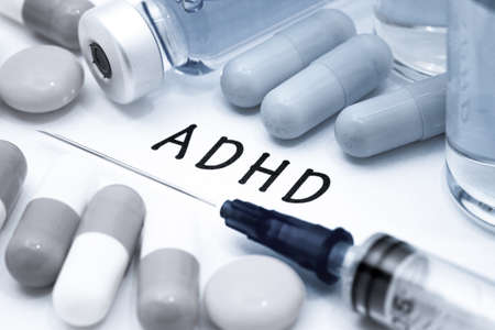inattention: ADHD - diagnosis written on a white piece of paper. Syringe and vaccine with drugs