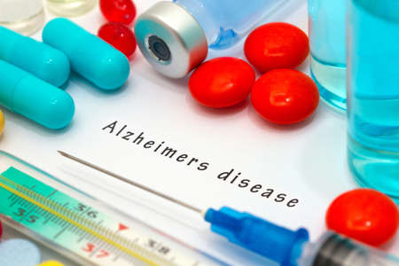 brain aging: Alzheimers disease - diagnosis written on a white piece of paper. Syringe and vaccine with drugs. Stock Photo