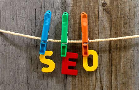 tweak: word seo fasten clothespins on a rope behind a wooden background