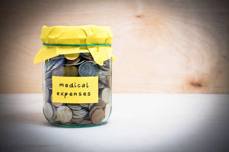 medical expenses: Financial concept. Coins in glass money jar with medical expenses label. Wooden background Stock Photo