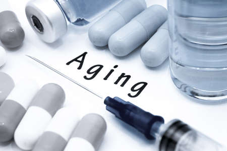 decrepitude: Aging - diagnosis written on a white piece of paper. Syringe and vaccine with drugs Stock Photo