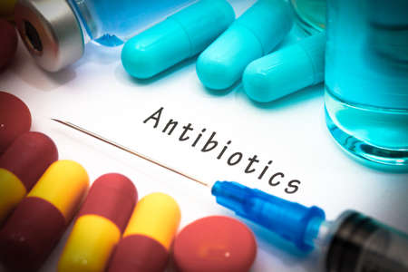 bacteria antibiotic: Antibiotics - diagnosis written on a white piece of paper. Syringe and vaccine with drugs. Stock Photo