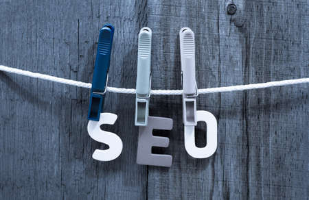 word seo fasten clothespins on a rope behind a wooden background