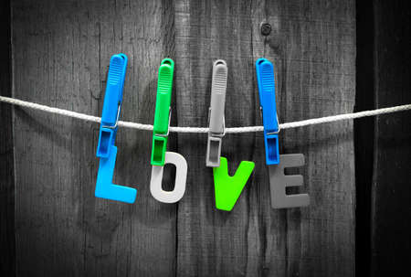 clothespins: word love fasten clothespins on a rope behind a wooden background